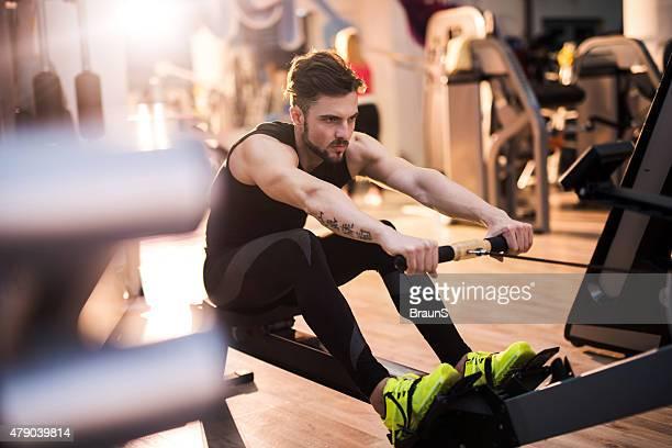 Déterminé Homme faisant de l'exercice sur un rameur dans une salle de sport.