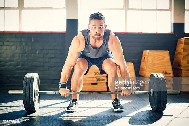 Determined man exercising while dead litfing barbell in gym