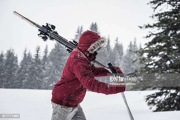 Determined skier walking through snow storm