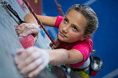 Determined teenage girl practicing rock climbing in fitness studio