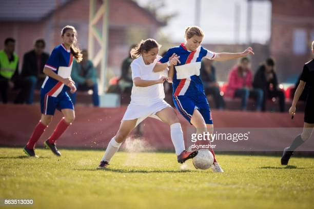 Determined teenage girls playing soccer on a sports match at stadium.