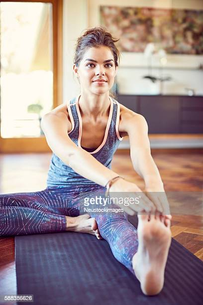 Determined woman doing stretching exercise on mat at home