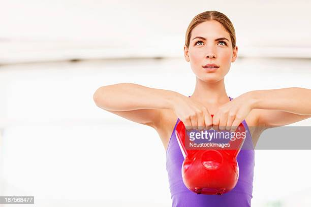 Determined Woman Lifting Kettle Bell At Gym
