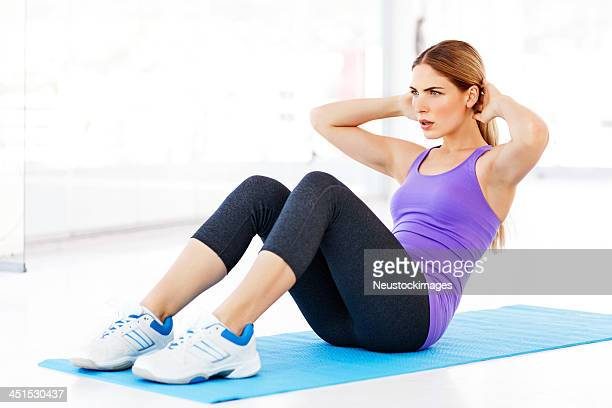 Determined Woman Looking Away While Performing Sit-Ups In Gym