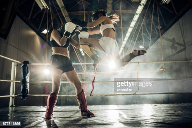 Determined woman making a flying move and kicking her opponent with a knee.