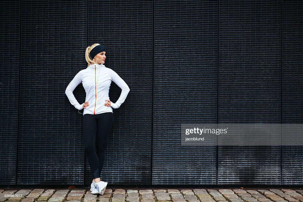 Determined woman resting after jogging in the city : Stock Photo