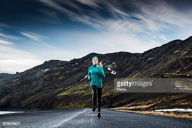 Determined woman running on road against mountain