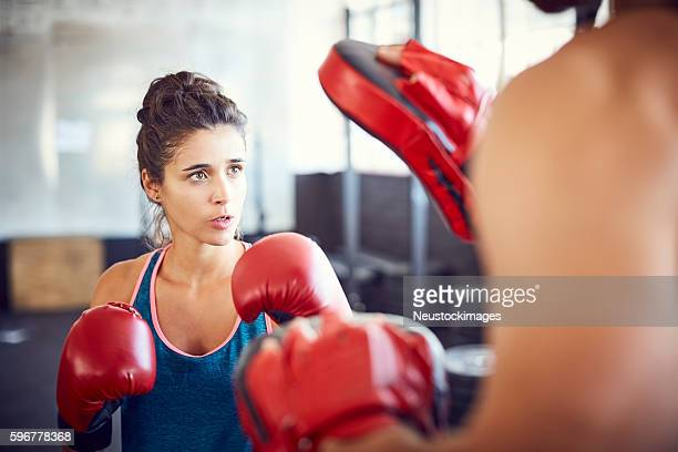 Determined young female fit boxer practicing in gym