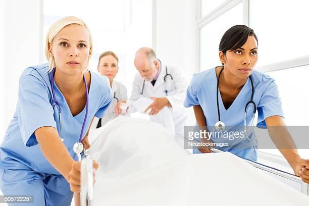 Déterminé de jeunes infirmières pousser Patient sur La civière