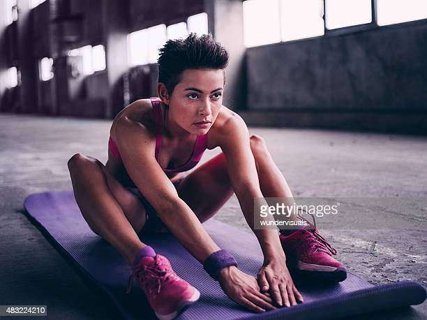 Determined young woman sitting on a colourful exercise mat