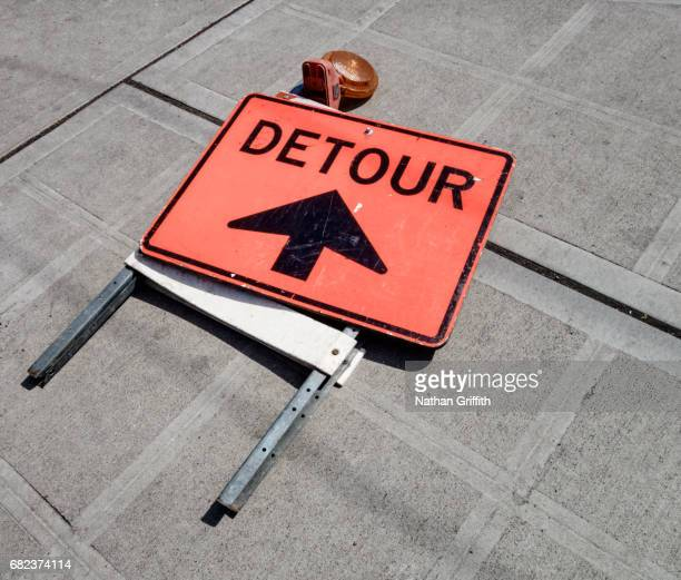 detour sign folded and laying on sidewalk