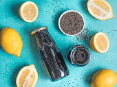 Detox activated charcoal black chia water or lemonade with lemon on bright blue background. Two bottle with black chia infused water. Detox drink idea and recipe. Vegan food and drink. Top view.