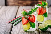 Infused detox water with  strawberry, lime and mint. Ice cold summer cocktail or lemonade in glass mason jar
