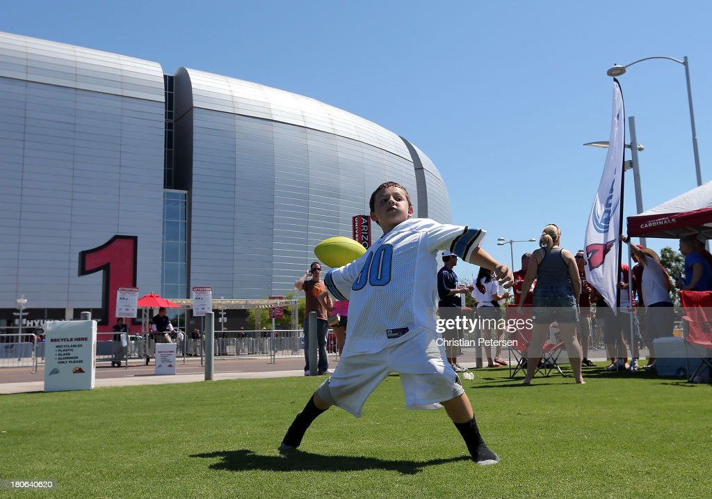 Detroit Lions fan, Tyler Watson of Palm Springs, CA plays football outside of University of Phoenix Stadium before the NFL game against the Arizona Cardinals on September 15, 2013 in Glendale, Arizona.