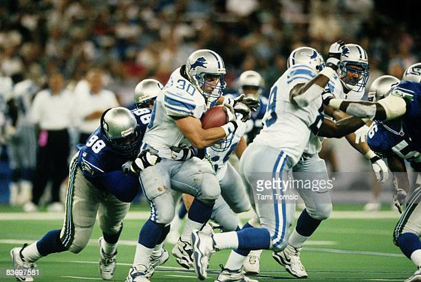 Detroit Lions fullback Cory Schlesinger tries to break the tackle of Seattle Seahawks defensive tackle Sam Adams during a 2820 Lions victory on...