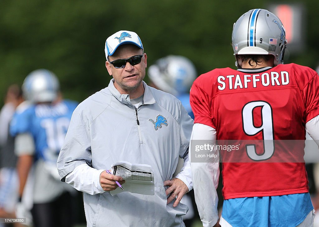 Detroit Lions Offensive Coordinator Scott Linehan talks with Quarterback Matthew Stafford #9 during the the third day of training camp on July 28, 2013 in Allen Park, Michigan.