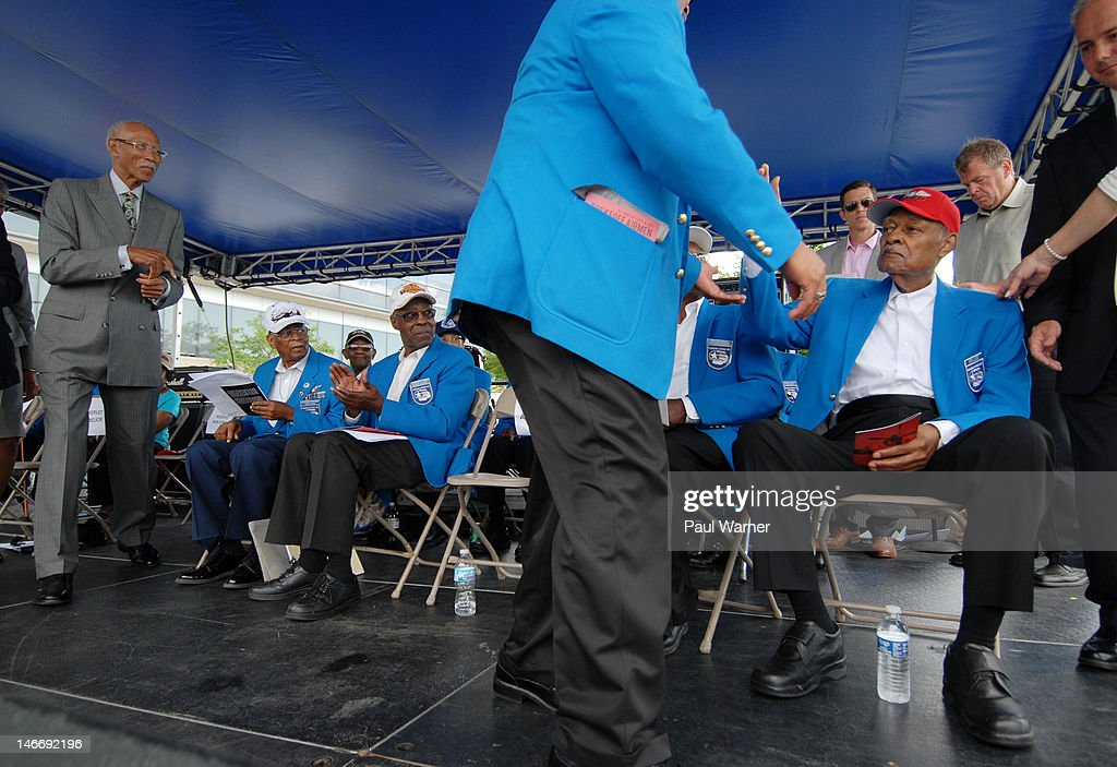 Detroit Mayor Dave Bing (L) and Tuskegee Airmen (seated L-R) Alexander Jefferson and Burton C. Lowe, clap for Airman Sandy G. Reid (far right, seated) at the opening ceremony salute to the Airmen at the 2012 Detroit River Days Festival at the Detroit RiverWalk on June 22, 2012 in Detroit, Michigan.
