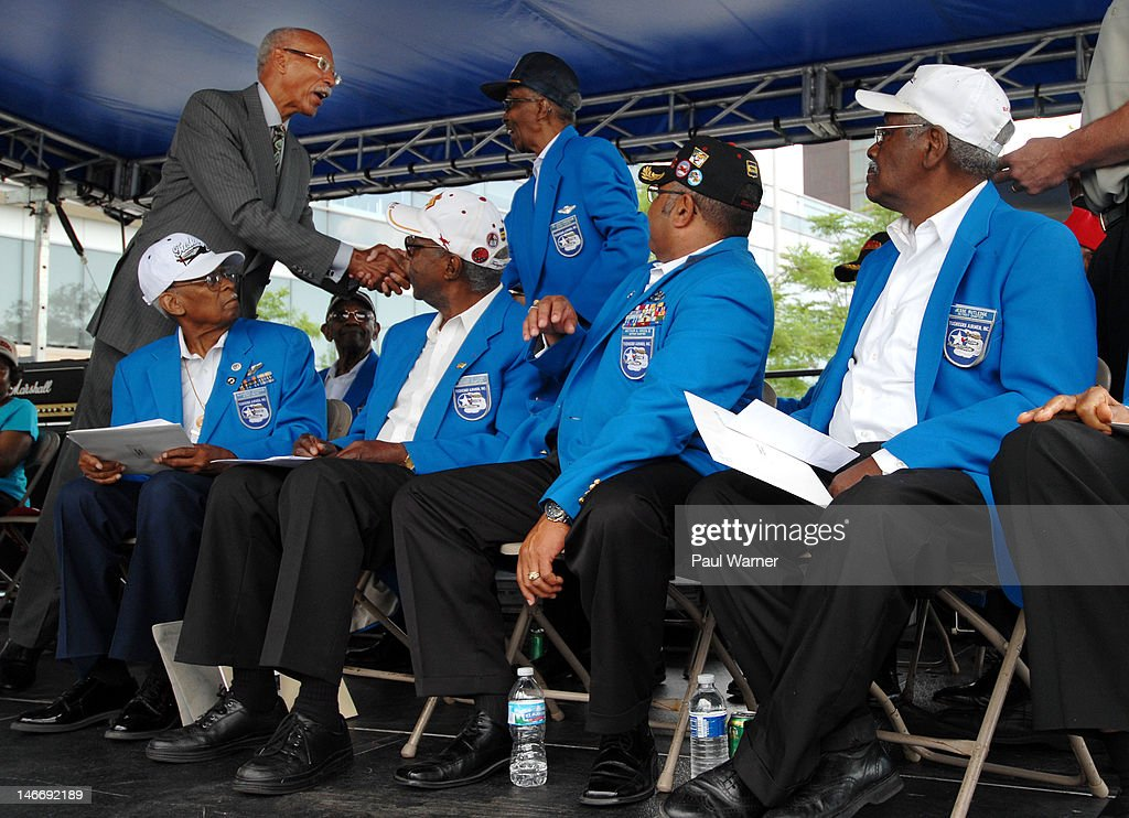 Detroit Mayor Dave Bing (top L) greets Tuskegee Airmen Dr. John Cunningham (top right) as Airmen (seated L-R) Alexander Jefferson,Burton C. Lowe, Arthur Green and Jesse Rutledge look on at the opening ceremony salute to the Airmen at the 2012 Detroit River Days Festival at the Detroit RiverWalk on June 22, 2012 in Detroit, Michigan.