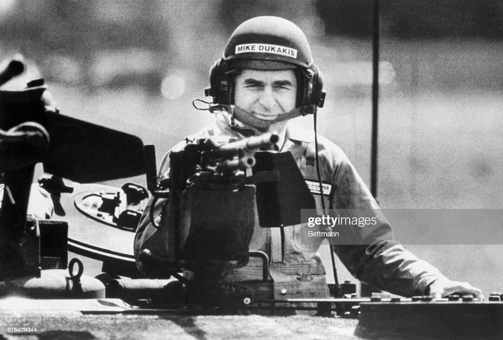 Presidential candidate, Mike Dukakis, wearing an army tanker's helmet, peers behind the loader's weapon of an MIAI Abrams Main Battle Tank during a demonstration ride tin the tank at he HQ of General Dynamics Land Systems Division in Detroit, where the tanks are manufactured. BPA2# 1433.