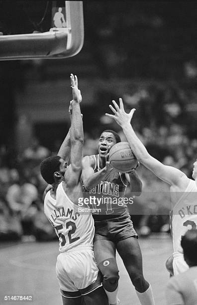 Detroit Piston Isiah Thomas attempts a shot over New Jersey Nets defender Buck Williams during the second quarter of a NBA basketball game East...