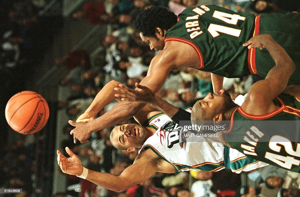 Detroit Pistons' Brian Williams (C) gets rid of the ball as he is trapped by the Seattle SuperSonics' Vin Baker (L) and Sam Perkins (R) in the fourth quarter 05 December at the Palace in Auburn Hills, MI. The SuperSonics beat the Pistons 94-89.AFP PHOTO/Matt CAMPBELL