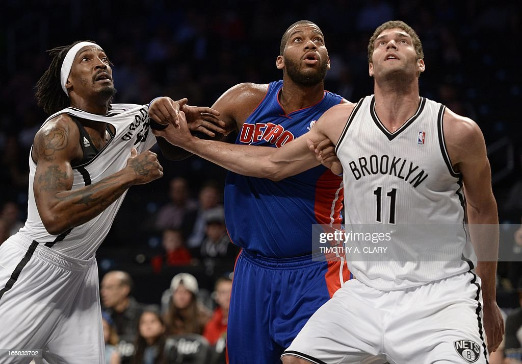 Detroit Piston's Greg Monroe (C) vies with Gerald Wallace (L) and Brook Lopez (R) of the Brooklyn Nets during their NBA game at the Barclays Center on April 17, 2013 in the Brooklyn borough of New York City. AFP PHOTO / TIMOTHY A. CLARY