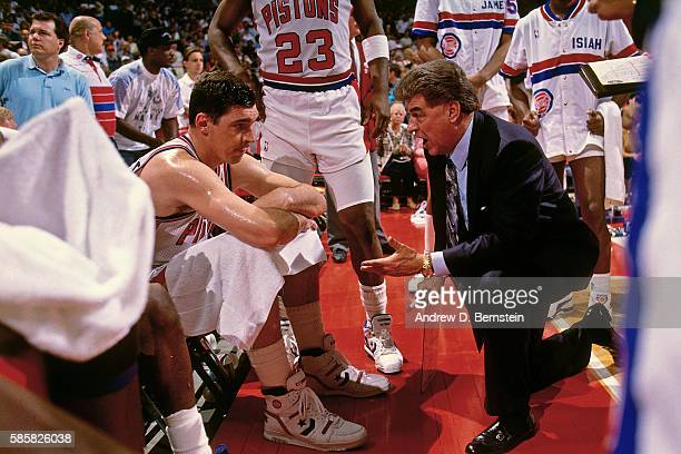 Detroit Pistons head coach Chuck Daly speaks to player Bill Laimbeer of the Detroit Pistons during a game circa 1991 at the Palace of Auburn Hills in...