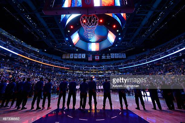 Detroit Pistons players foreground and the Los Angeles Lakers stand as the French national anthem is played in honor of the victims of the terrorist...
