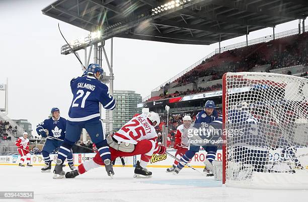 Detroit Red Wings alumni Darren McCarty battles for a loose puck with Toronto Maple Leafs alumni Borje Salming and Dmitri Yushkevich in front of...