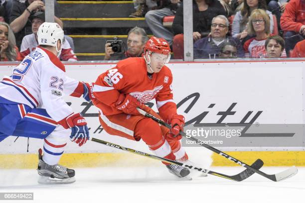 Detroit Red Wings center Ben Street turns for the puck away from Montreal Canadiens defenseman Mikhail Sergachev during the NHL hockey game between...