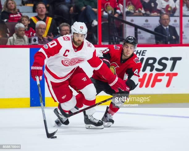 Detroit Red Wings Center Henrik Zetterberg stickhandles the puck against Ottawa Senators Center JeanGabriel Pageau during the NHL game between the...