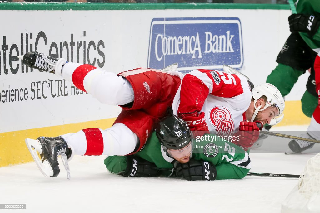 Detroit Red Wings Defenceman Mike Green (25) falls on top of Dallas Stars Center Radek Faksa (12) during the NHL game between the Detroit Red Wings and Dallas Stars on October 10, 2017 at the American Airlines Center in Dallas, TX.