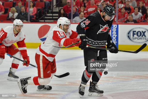 Detroit Red Wings Defenceman Robbie Russo hits Carolina Hurricanes Right Wing Phillip Di Giuseppe in the back as he tries to play a puck in the...