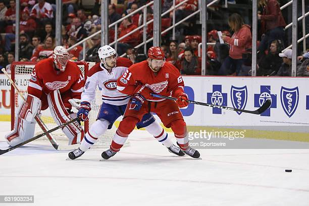 Detroit Red Wings defenseman Xavier Ouellet of France and Montreal Canadiens forward Phillip Danault chase after the puck during the second period of...