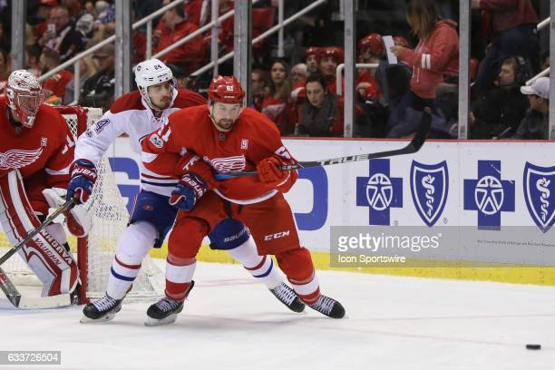 Detroit Red Wings defenseman Xavier Ouellet of France and Montreal Canadiens forward Phillip Danault chase after the puck during a regular season NHL...