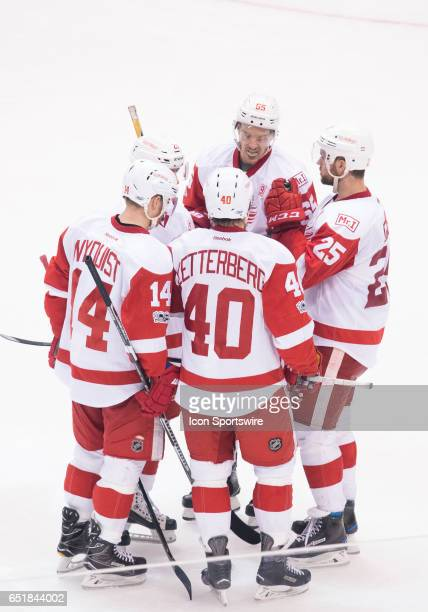 Detroit Red Wings left wing Henrik Zetterberg takes with Detroit Red Wings defenseman Niklas Kronwall and Detroit Red Wings right wing Gustav Nyquist...