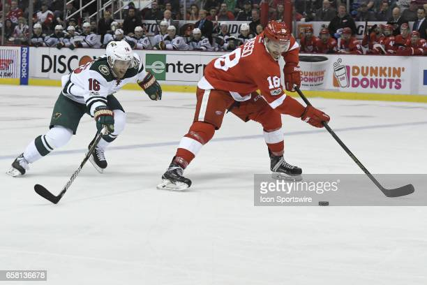 Detroit Red Wings Robbie Russo D and Minnesota Wild Left Wing Jason Zucker battle for the puck during NHL hockey game between the Minnesota Wild and...