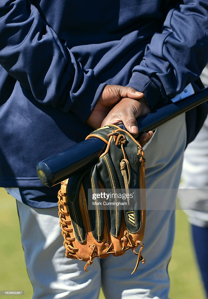 A Detroit Tigers coach holds his baseball glove and bat during Spring Training workouts at the TigerTown Facility on February 18, 2013 in Lakeland, Florida.