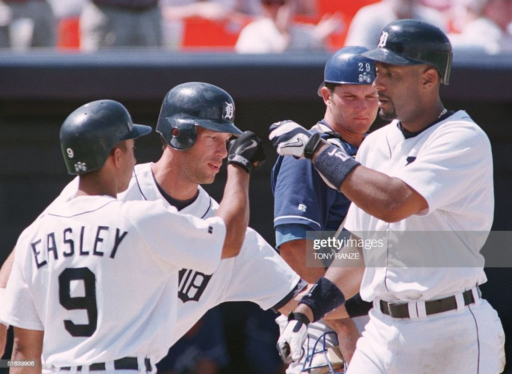 Detroit Tigers' first baseman Tony Clark is congratulated by Tigers' outfielder Luis Gonzalez and second baseman Damion Easley after hitting a tworun...
