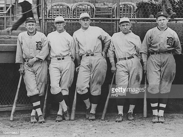 Detroit Tigers hitters Ty Cobb Rip Collins Ike Boone Bucky Harris and Harry Heilmann stand leaning against their baseball bats while in their kits...