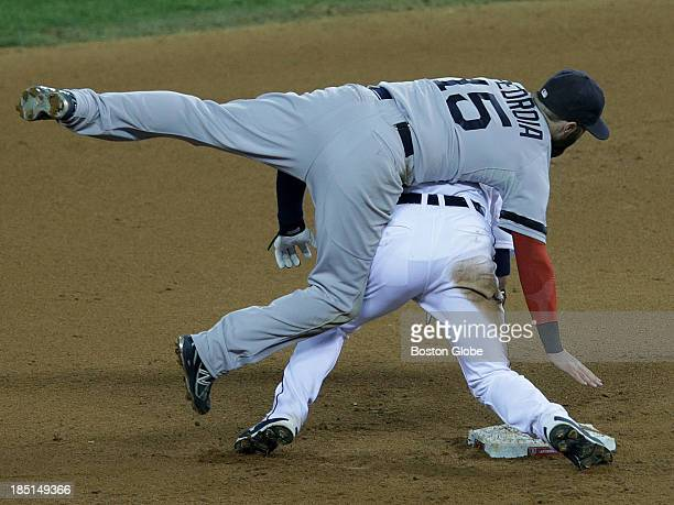 Detroit Tigers shortstop Jose Iglesias slides hard into Boston Red Sox second baseman Dustin Pedroia to break up the double play in the sixth inning...