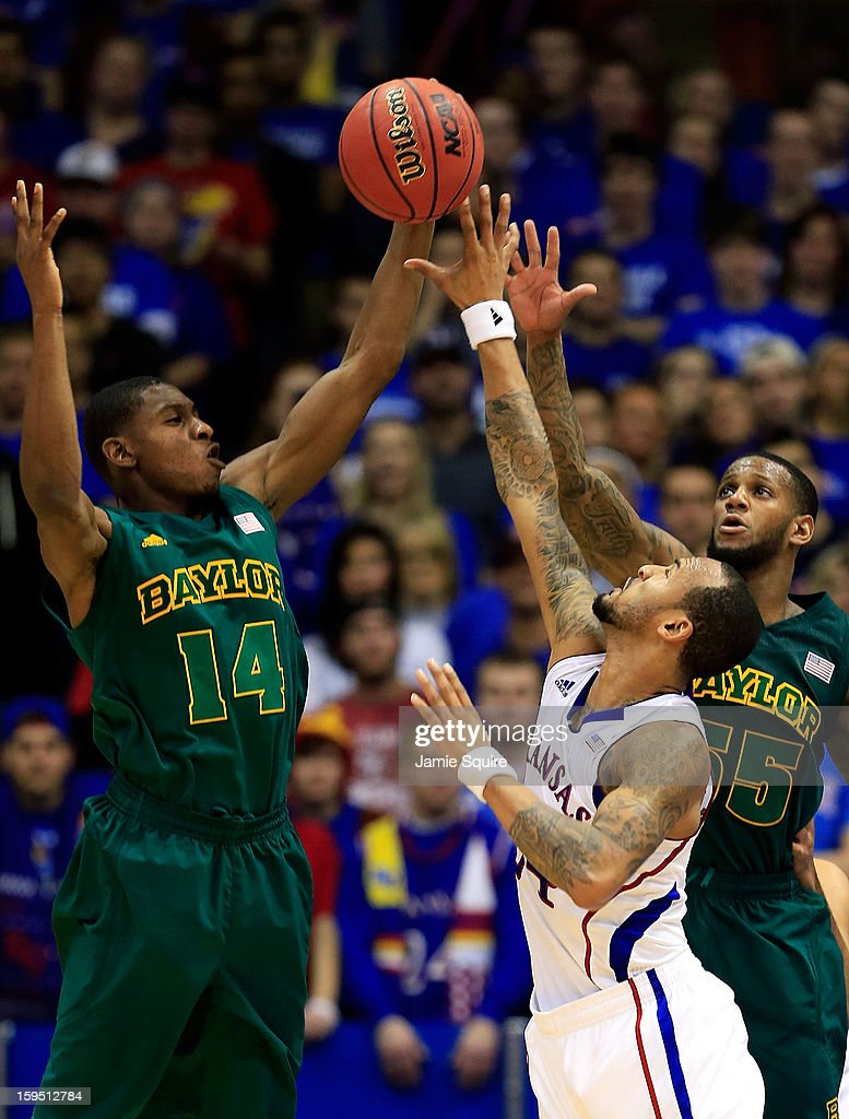 Deuce Bello #14 and Pierre Jackson #55 of the Baylor Bears compete with Travis Releford of the Kansas Jayhawks for a loose ball during the game at Allen Fieldhouse on January 14, 2013 in Lawrence, Kansas.
