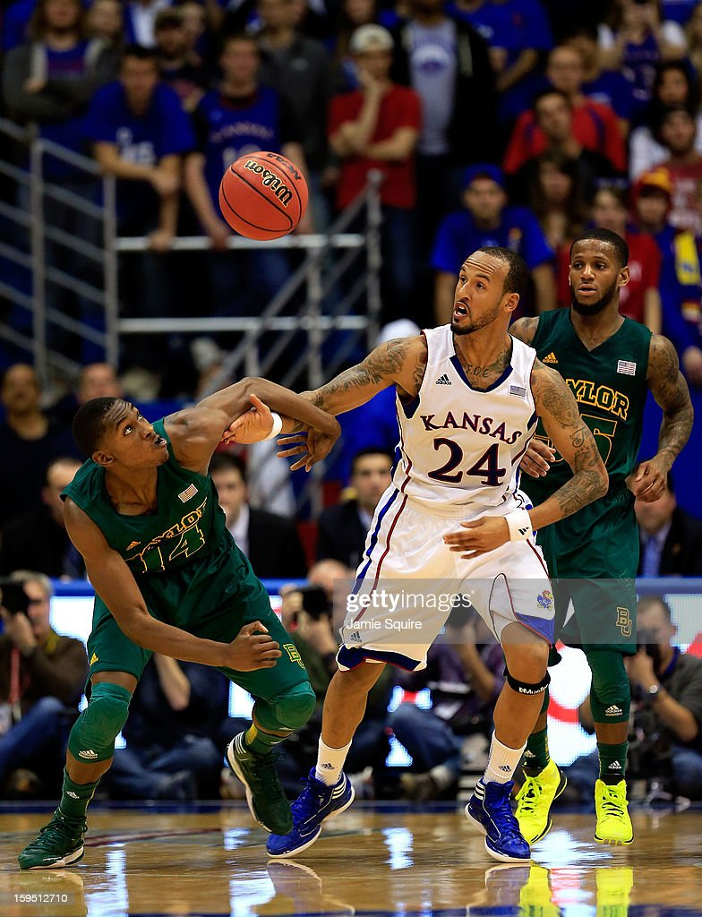 Deuce Bello #14 of the Baylor Bears and Travis Releford #24 of the Kansas Jayhawks compete for a loose ball during the game at Allen Fieldhouse on January 14, 2013 in Lawrence, Kansas.
