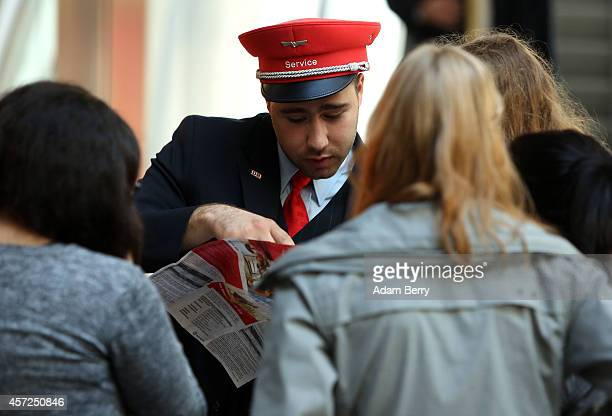 Deutsche Bahn employee gives passengers information at the central station in Berlin as train employees strike on October 15 2014 in Berlin Germany...