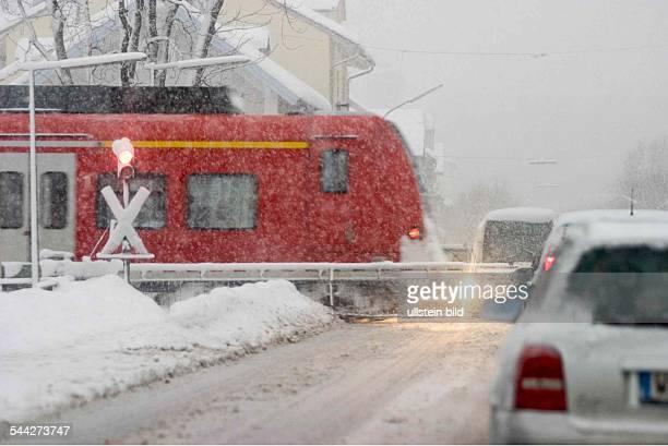 Deutschland Bayern Penzberg Autos warten am am Bahnübergang im Schneegestöber ein Regionalzug der Deutschen Bahn fährt vorbei