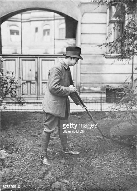 Deutschland Berlin Städtisches Berufsamt Junger Mann bei der Gartenarbeit mit der Harke 'Zeichen unserer Armut' Berliner BildBericht