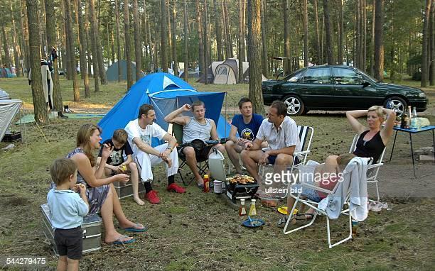 Camper auf einem Campingplatz beim Grillen