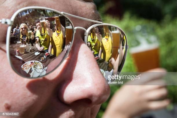 DEU Deutschland Germany Berlin Biertrinken im Biergarten Szene gespiegelt in den Gläsern einer Sonnenbrille