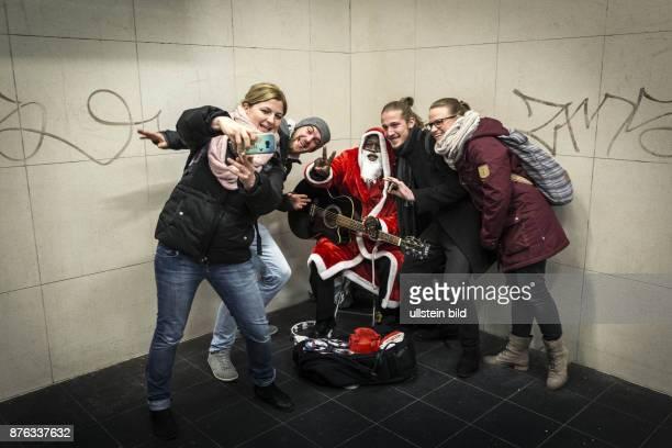 DEU Deutschland Germany Berlin Ein dunkelhäutiger Sänger als Weihnachtsmann verkleidet spielt Gitarre in der UBahnstation Stadtmitte
