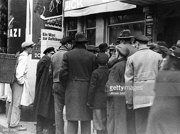 Deutschland III Reich Saarland Volksabstimmung ueber Status Diskussionsgruppe vor einerLitfaßsäule mit Propagandaplakatenfür die Abstimmung über den...